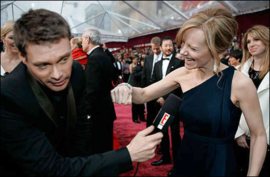 Ryan Seacrest shoves a microphone at Amy Ryan