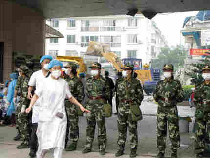 Hospital workers outside the traditional Chinese Medicine Hospital in Dujiangyan, China, in 2008. Ph