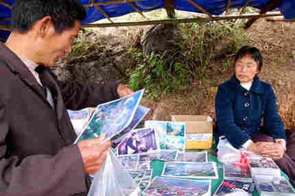 Local vendor Mu Zhenxian lost 16 relatives in the quake. She now sells photos and DVDs of earthquake