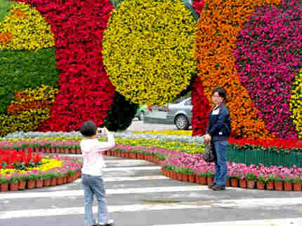 A young girl takes a picture of her mom in front of a May Day display in Chengdu, China. Photo: Meli