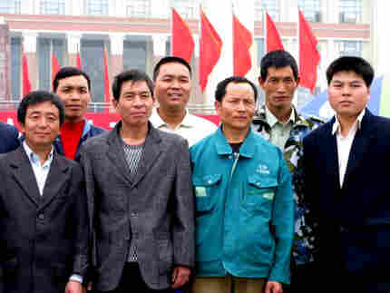 A group of me pose for a photo in front of the iconic statue of Chairman Mao in Tianfu Square in Che