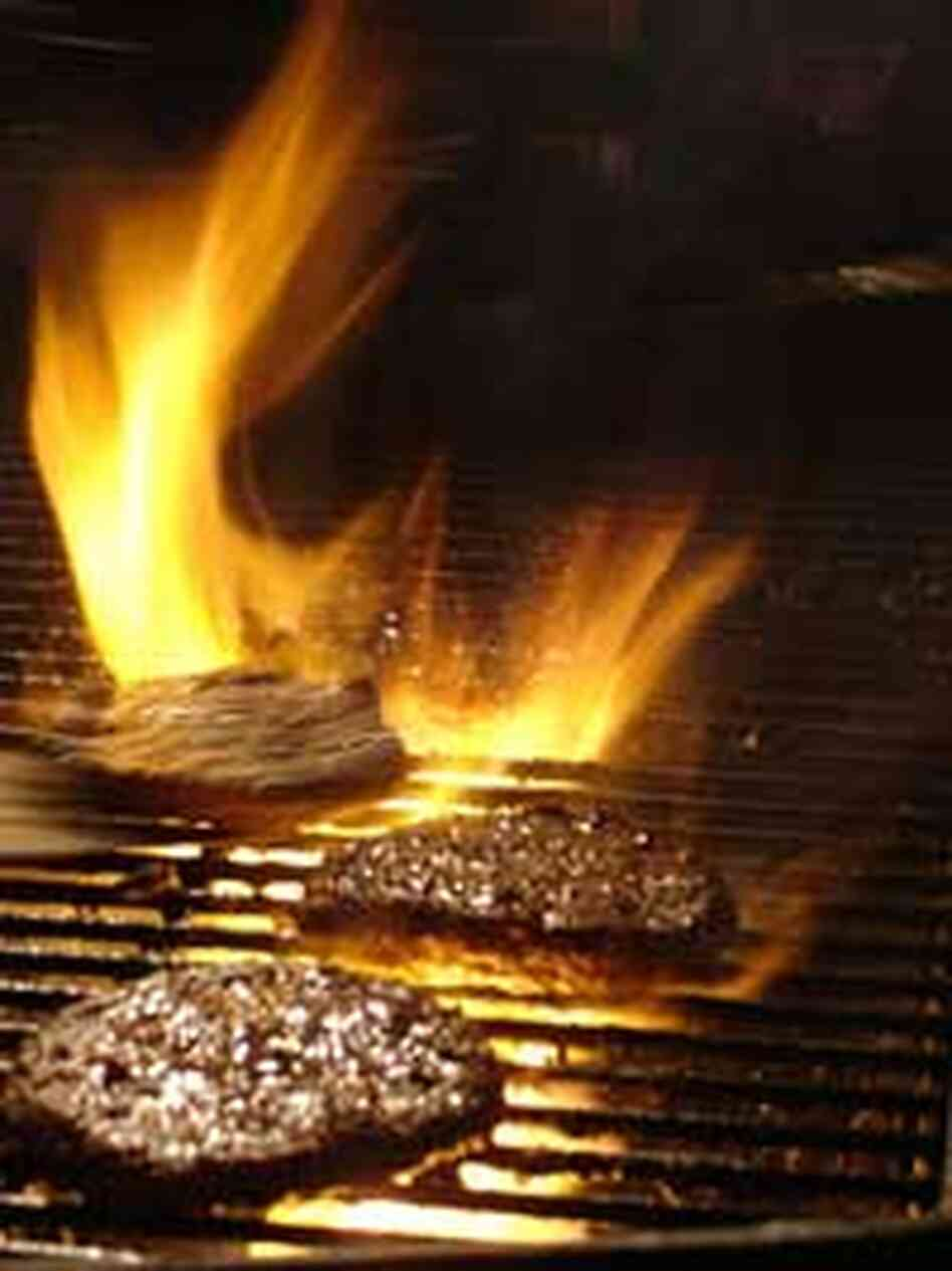 juicy hamburgers cooking on a flaming grill