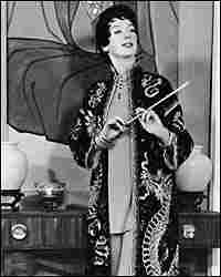 Rosalind Russell, as Auntie Mame, in a kimono with cigarette holder
