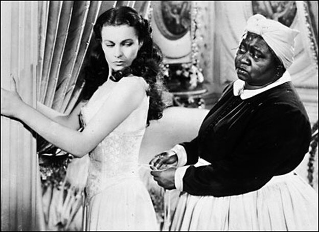 Mammy (Hattie McDaniel) laces up the stays of Scarlett O'Hara's (Vivien Leigh's) corset