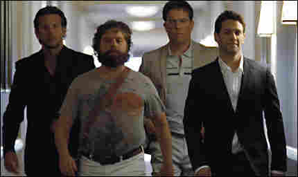 Bradley Cooper, Zach Galifianakis, Ed Helms, and Justin Bartha marching down a hallway in 'The Hango
