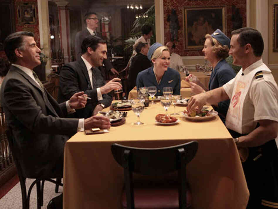 Don Draper (Jon Hamm) and Salvatore Romano (Bryan Batt) have dinner with friends on the season premi