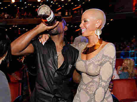 Kanye West drinks from a bottle and stands with Amber Rose at the MTV Video Music Awards on Septembe