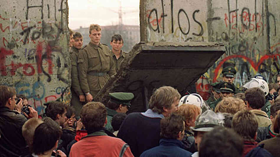 A crowd watches on November 11, 1989 as border guards demolish a piece of the Berlin Wall.