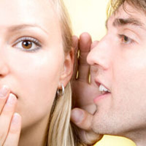 man whispering to a woman.