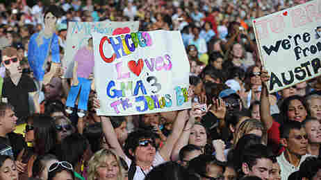 Fans hold up signs at a Jonas Brothers concert.