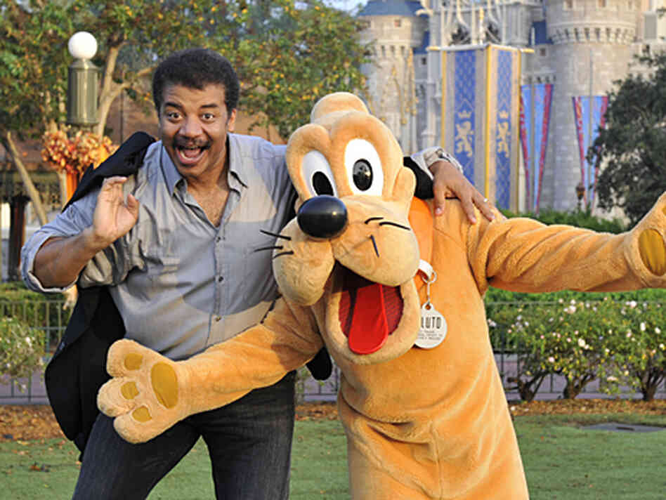 Astrophysicist Neil deGrasse Tyson poses with a costumed Pluto the dog.