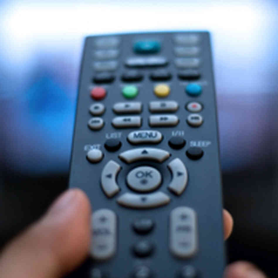 a thumb pushing a remote control button