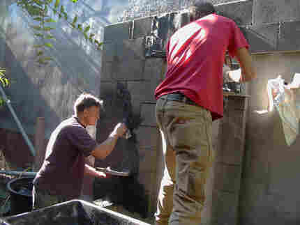 applying stucco to cinder block carcass of fountain