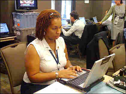 TMM Producer Teshima Walker files production notes at NPR's workspace at the Democratic National C