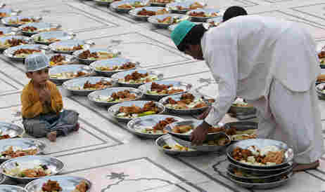 A Pakistani Muslim arranges food stuff for 'Iftar', a time to break the fast, on the first day of ho