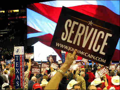 """Crowd members wave signs of """"Service"""" for GOP nominee Sen. John McCain at the Republican National"""