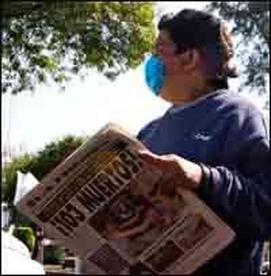 A pedestrian reads a newspaper, which headline states that up to 103 deaths due to the swine flu,