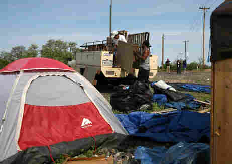 """Earnest Thomas, a homeless man, moves his belongings at a homeless """"tent city"""" in Sacramento, Calif."""