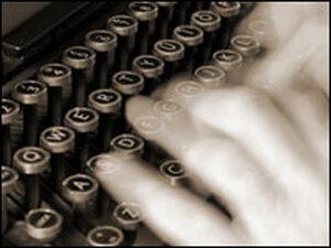 Hands typing on a typewriter.