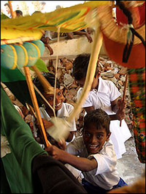 Young Sri Lankan tsunami survivors play with puppets.