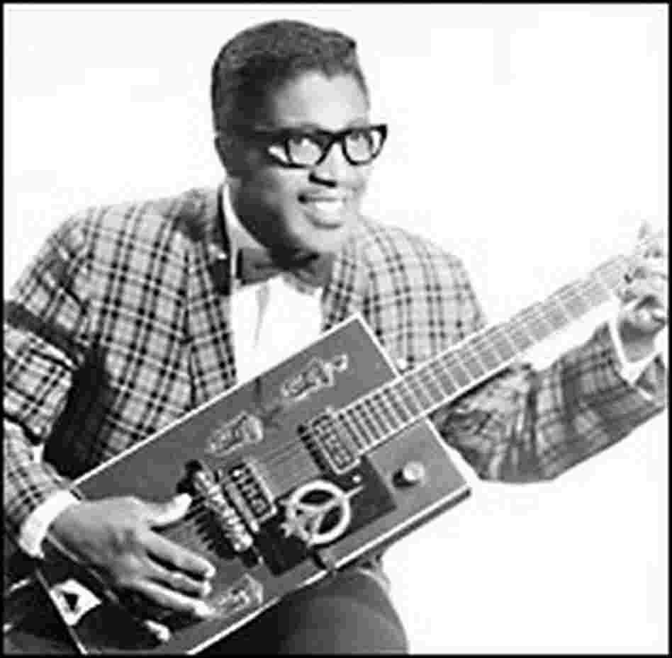Bo Diddley pictured in the late 1950s, poses with his guitar.