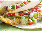 The fish taco is made by placing hot, crispy fried fish on a lightly charred corn tortilla