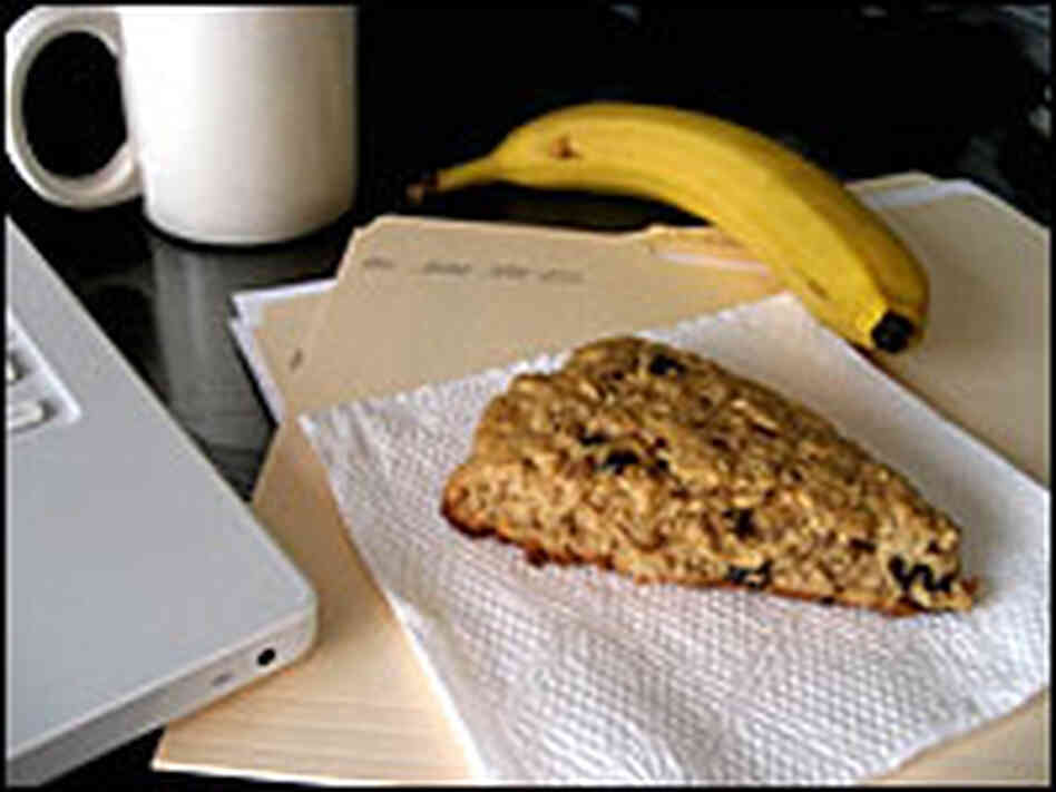 A scone is nestled on a napkin, completing a desktop breakfast with coffee and banana