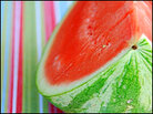 Half of a ripe, juicy watermelon sits on a colorful striped cloth