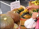 A customer selects acorn squash from a display at a farmers market