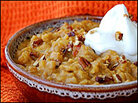 A bowl of 'Pumpkin Pie Risotto' topped with candied pecans and whipped cream