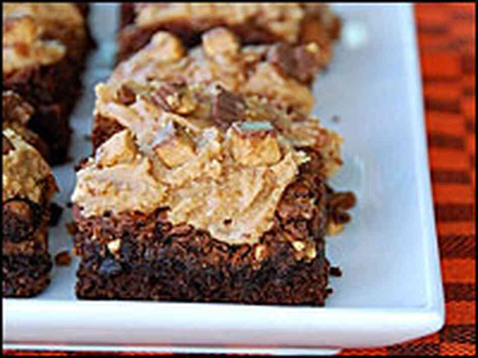 A white platter of Reese's Peanut Butter Cup Brownies sits on an orange-checkered cloth