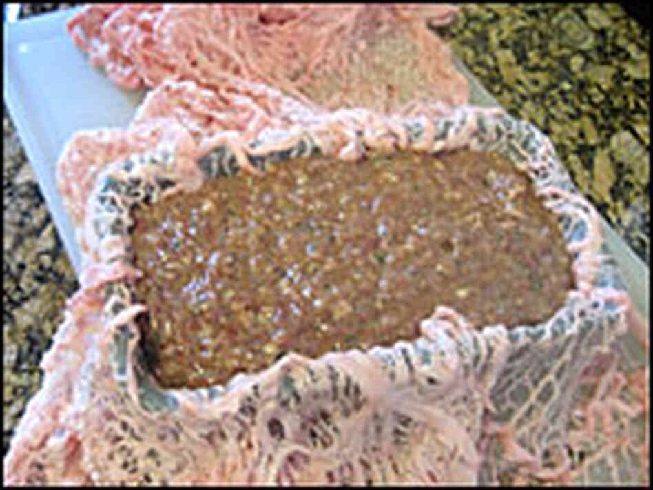 A loaf pan is lined with lacy caul fat and packed with ground, seasoned meat