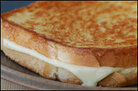 White cheese oozes out of a golden-brown grilled cheese sandwich