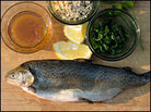 A fresh trout sits on a cutting board with other ingredients for Pan-Fried Trout With Brown Butter