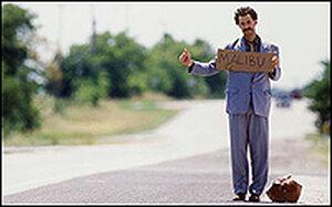 Sacha Baron Cohn as 'Borat' holds a sign saying 'Malibu.'