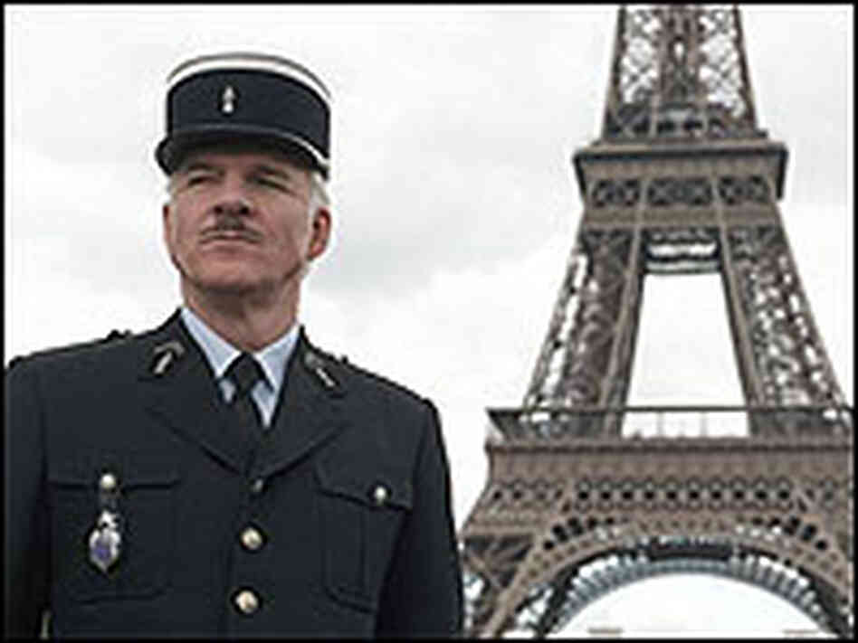 Steve Martin as Inspector Jacques Clouseau, posing with the Eiffel Tower as a backdrop.