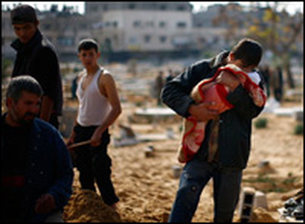 Bilal Soboh, 19, holds the body of his 20-day-old baby girl, who died in the morning, before burial in a grave dug by hand Jan. 19, 2008. The family had tried to get help for the ailing baby but it was too dangerous to leave their home in Tuam, in the northern Gaza Strip during the fighting between Hamas and the Israelis.