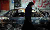 A Palestinian woman walks past a burned car in northern Gaza, Jan. 19.