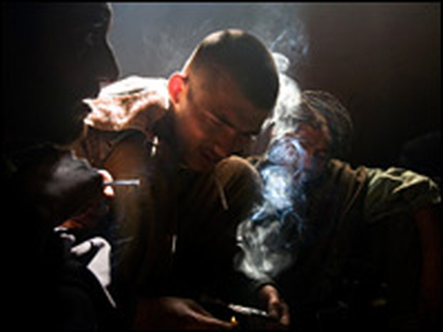 Addicts light up in a dilapidated room at the former Russian Cultural Center in Kabul. Users melt the heroin paste, then inhale the smoke byproduct to feel the effects of the drug.