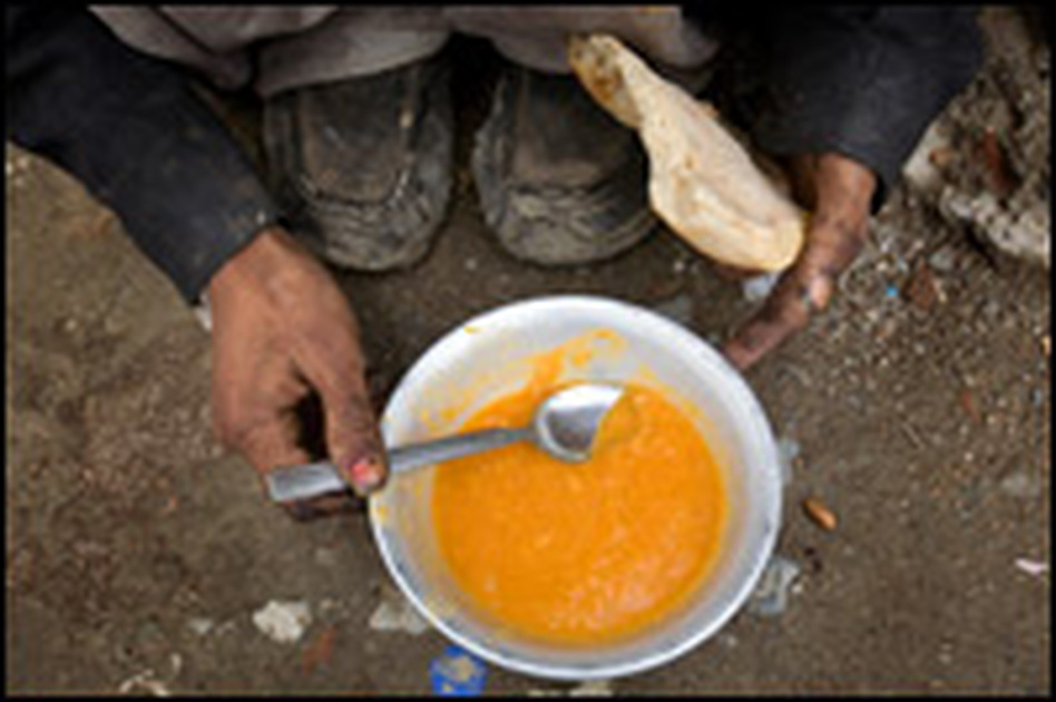 A man sits hunched over his lunch. A U.N. initiative feeds about 650 people a day. Each person receives one daily meal — soup, bread and a little fruit for lunch.