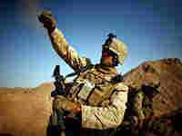 Cpl. Daniel Clift tosses a handful of rocks to simulate tossing a smoke grenade in Afghanistan.