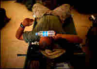 A Marine uses a water bottle to cool down inside of the non-air-conditioned ten