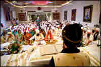 During a wedding ceremony, Sada Sat Sinran Singh reads from a book of sacred writings