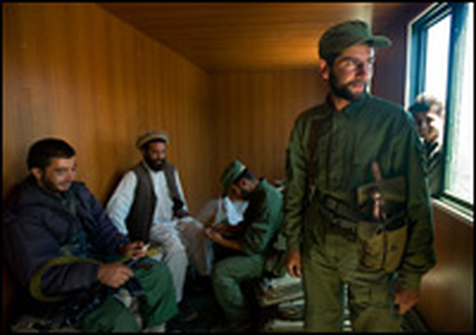 Afghan Public Protection Force members, known as Guardians, and a community elder make themselves at home inside a container used as a new checkpoint near the village of Badam Kalay, in Wardak province, Afghanistan.