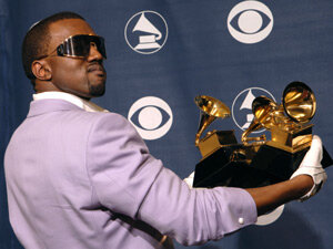 Kanye West shows off his Grammy haul after the 2006 awards.