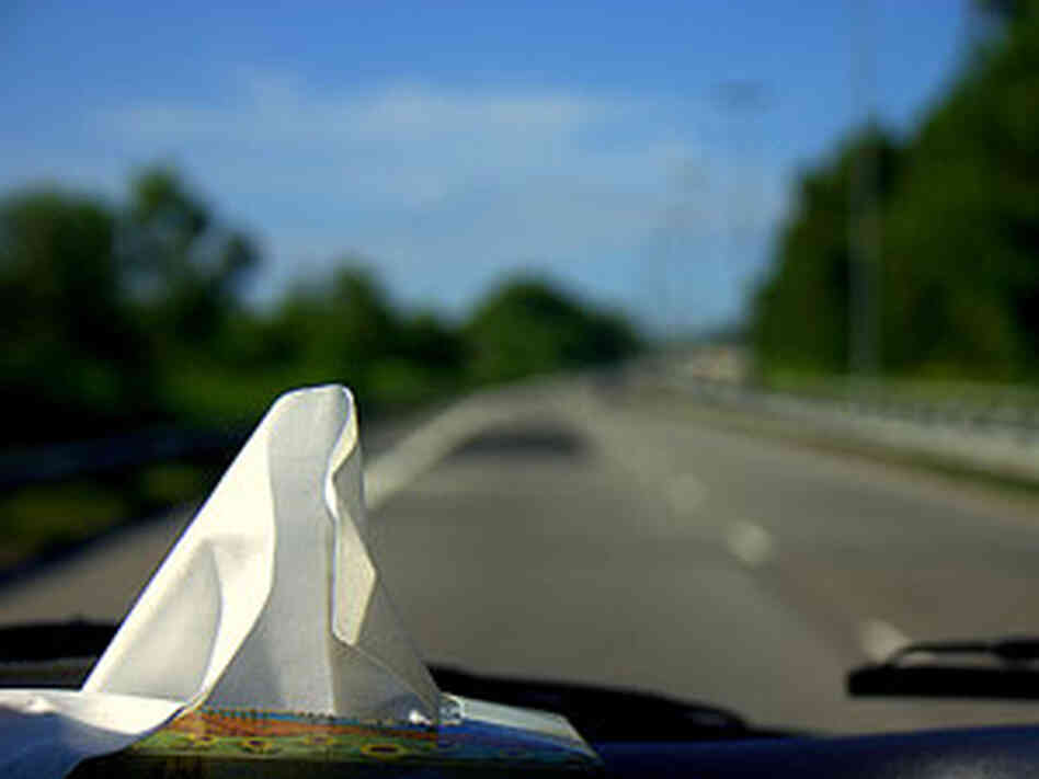 300 a box of tissues sits on a car's dashboard