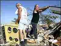 Charles Zimmerman (left) clears debris after his mobile home in Punta Gorda, Florida.