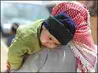An Iraqi refugee carries his son at a refugee camp near the far eastern Jordanian town of Ruweished,