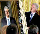 Former President Bill Clinton looks at his official portrait