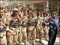 Members of the Iraqi National Guard show their support at a rally in Najaf for al-Sistani